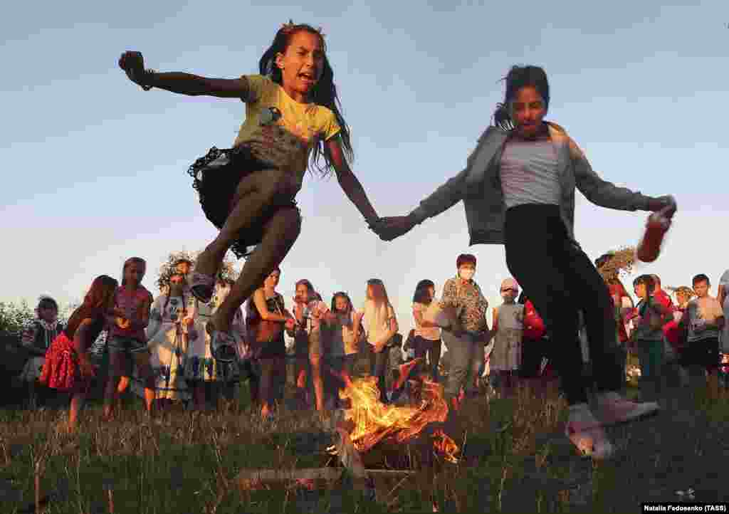 Girls jump over a bonfire.