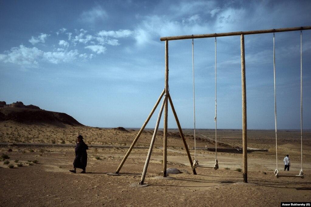 A set of swings in the dusty expanse of the desert of Karakalpakstan in the north of Uzbekistan.