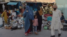 A burqa-clad Afghan woman looks for items to buy at a shop displaying used household items for sale at a market area in Kabul.