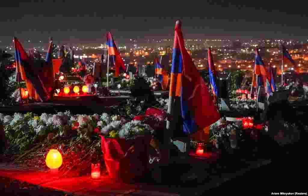 Ерменски знамиња и свеќи ги покриваат воените гробишта Јераблур во Ереван на 18 декември. Фотографијата е направена во пресрет на тридневната национална жалост за оние кои загинаа војувајќи против азербејџанските сили во и околу отцепената област на Азербејџан, Нагорно Карабах.