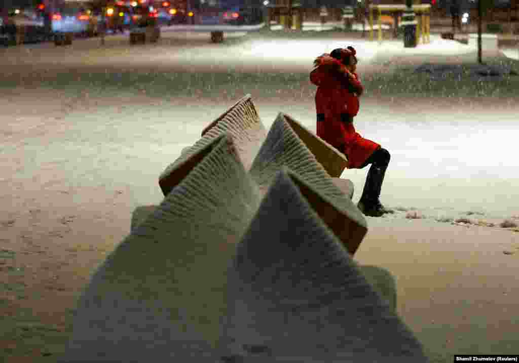 A woman sits on a bench as she poses for a picture during a snowfall in Almaty, Kazakhstan, on February 6. (Reuters/Shamil Zhumatov)