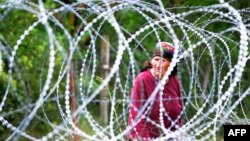 A woman looks through 1.2-meter-high coils of razor wire that divide the Russian-backed breakaway territory of South Ossetia from Georgian-controlled land in village of Khurvaleti.