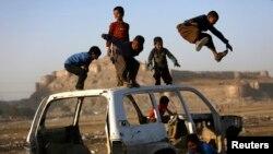 Мальчики играют у разобранного автомобиля. Кабул, 22 октября 2013 года.