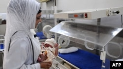 A doctor places a newborn baby into an incubator at the Lady Aitchison hospital in Lahore, Pakistan.