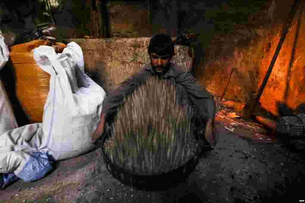 Афганский рабочий готовится жарить семена на фабрике в Герате