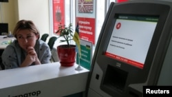 An employee sits next to a payment terminal out of order at a branch of Ukraine's state-owned Oschadbank in Kyiv on June 27.