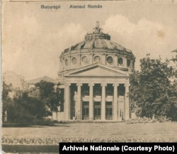 """Societatea """"Ateneul Român"""" a fost înființată în 1865 de boierul Constantin Esarcu cu scopul de promova artele și știința. Esarcu a lăsat prin testament 200.000 de galbeni (lei aur) pentru ridicarea """"clădiri monumentale"""". În anii '50, guvernul pro-sovietic a dorit să distrugă marea frescă a istoriei naționale ce înconjoară sala principală. Relații personale și inspirația unui administrator a făcut ca ocupații să se mulțumească cu acoperirea ei cu o pânză roșie. Plăcile comemorative cu numele donatorilor au fost însă sparte. Se află în subsolul clădirii așteptându-și restaurarea. Foto: Arhivele Naționale"""