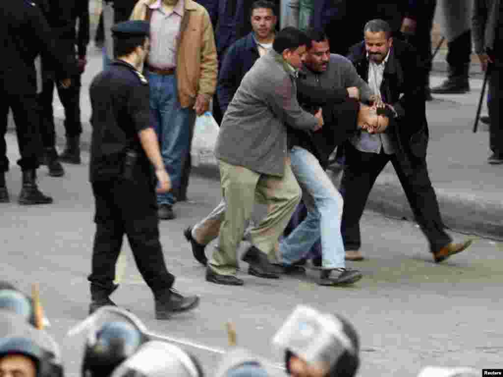 Полицейские задерживают участника антиправительственной демонстрации в Каире