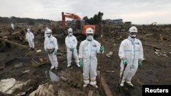 Japanese police officers in protective suits observe a moment of silence for those who were killed by the March 11 earthquake and tsunami as they search for bodies at a destroyed area in Minamisoma, Fukushima prefecture, in April 2011.