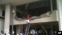 Пожарные и спасатели проводят работы на месте взрыва около здания ООН. Абуджа, 26 августа 2011 года.