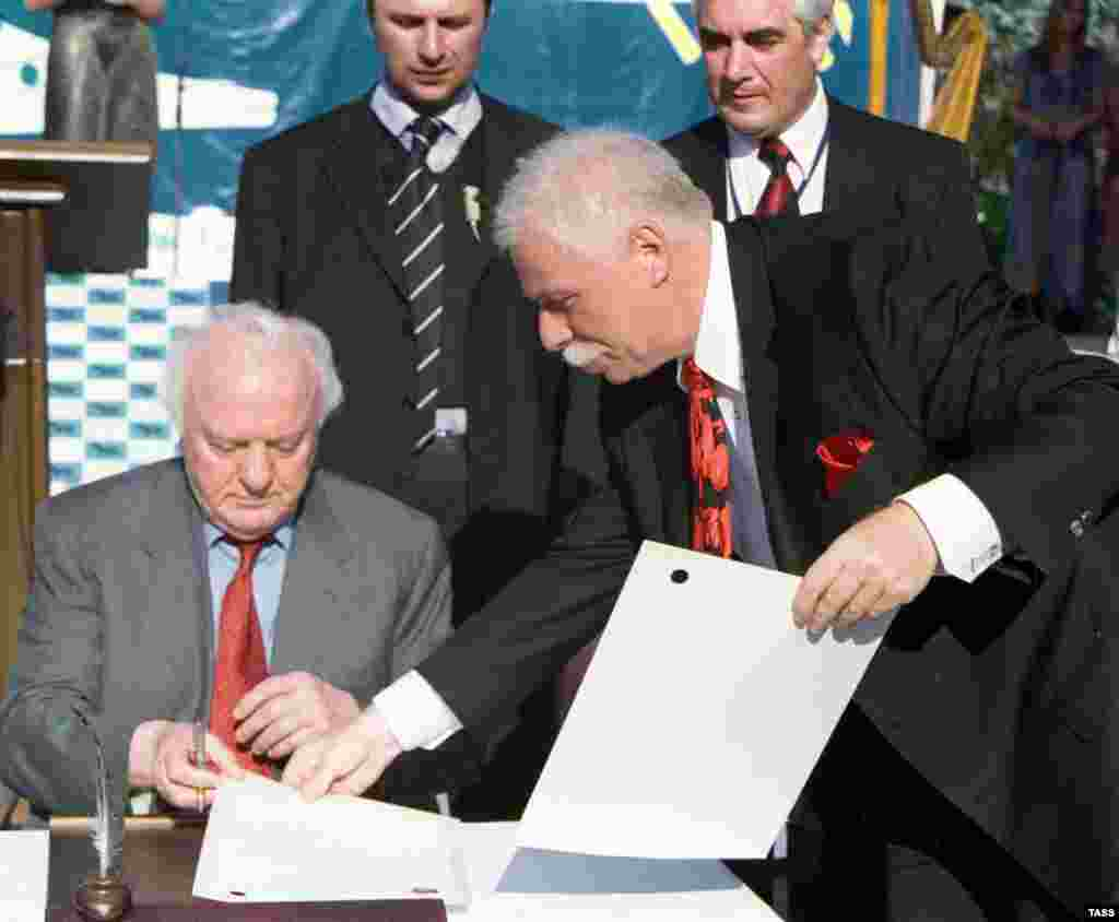 """GEORGIA -- 21AUG2003. Georgian President Eduard Shevardnadze (L) and well-known businessman Badri Patarkatsishvili (R) signed documents on the beginning of construction a health resort """"Imedis Kalaki """"(Town of Hope) located between the cities of Poti and"""