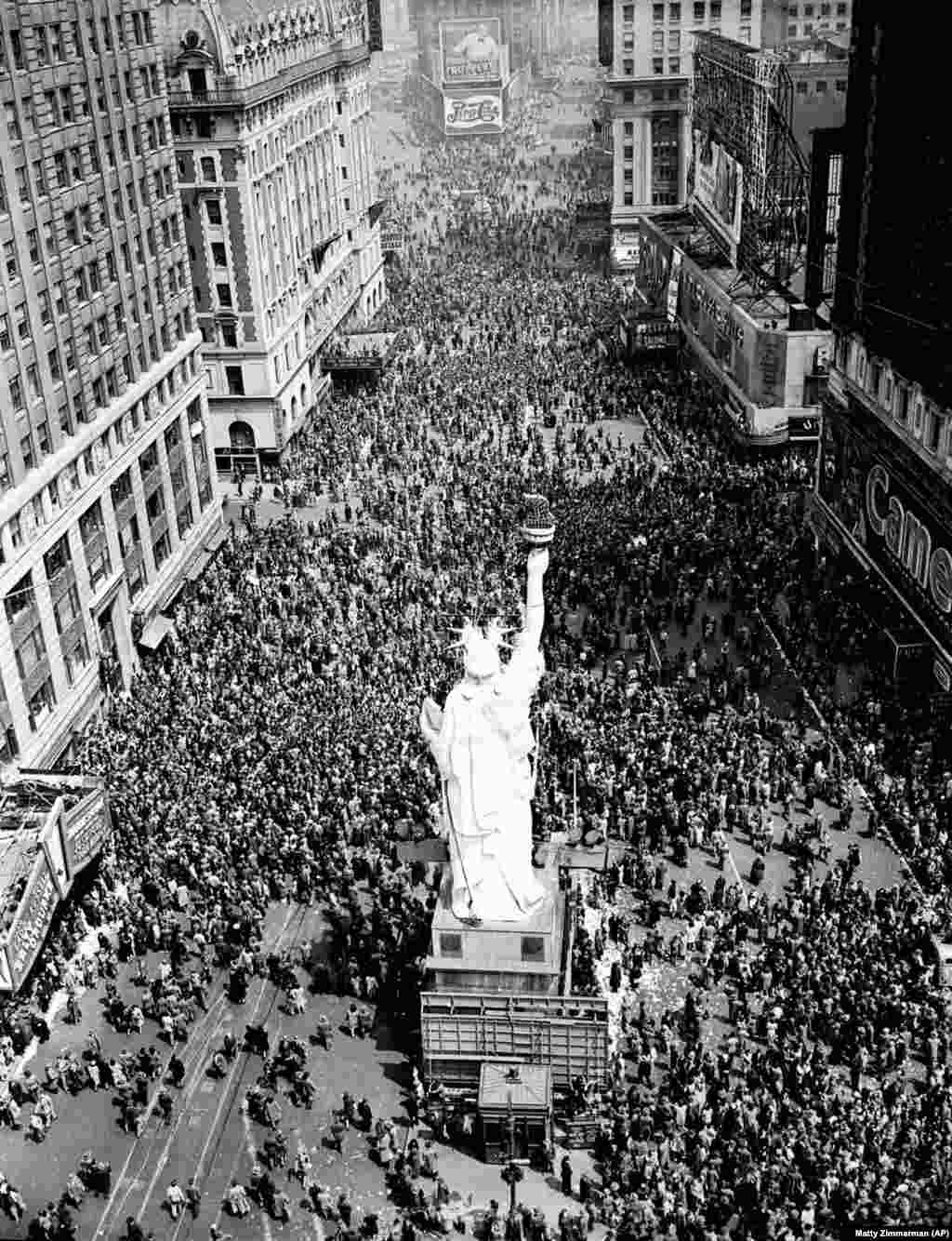 "Crowds gather under a replica of the Statue of Liberty on Times Square. A reporter described the giddy scene: ""Here and there, a tipsy civilian – sometimes a serviceman – offered drinks to strangers. The drinks were eagerly accepted, mostly by teenagers."""