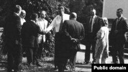 На цьому фото, що, за словами спецпрокурора Роберта Мюллера, було зроблене на вказівку Манафорта, тодішній президент Віктор Янукович (у центрі) зображений разом із радником і депутатом від Партії регіонів Ганною Герман (друга праворуч), старшим сином Олександром Януковичем (крайній ліворуч) і Миколою Злочевським, колишнім міністром екології (другий ліворуч). Розмова з кількома невстановленими людьми відбувається в невідомому місці, найімовірніше, в резиденції Януковича «Межигір'я»