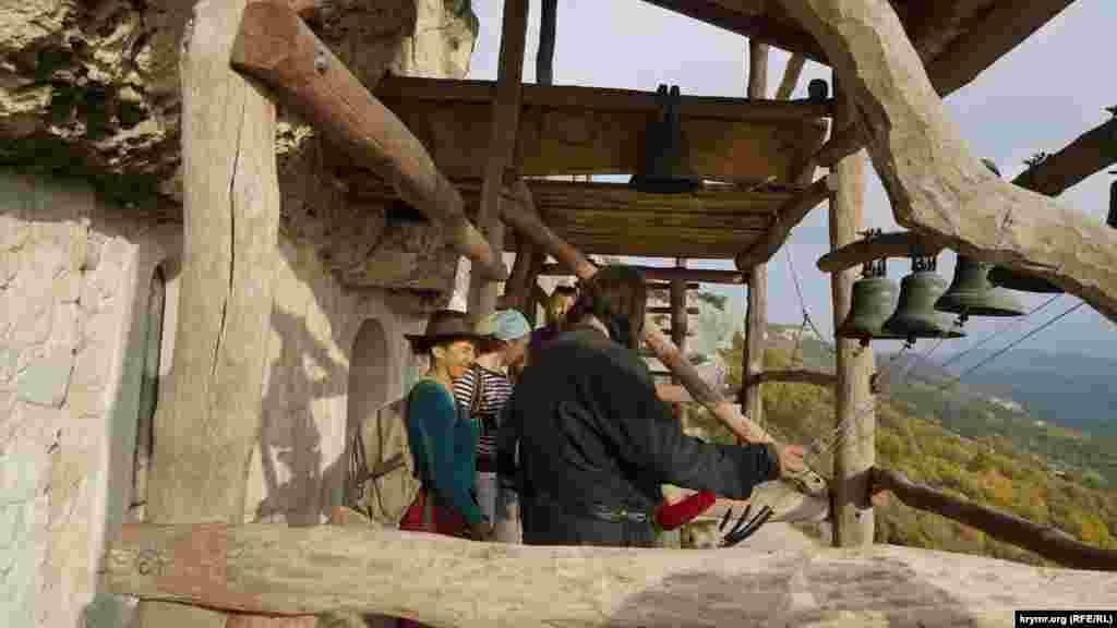 Единственный проживающий в монастыре монах Варсанофий показывает туристам как правильно бить в церковные колокола. Вместе в Варсанофием в монастыре живут еще три послушника