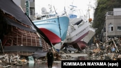 In this file picture from April 28, 2011, fishing vessels are shown washed ashore, amid the fire-ravaged Shishiori district of the port city of Kesennuma, weeks after a devastating tsunami hit Japan.