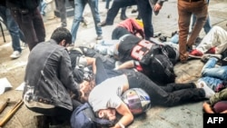 Injured protesters lie on the ground as Turkish riot police fire tear gas to disperse demonstrators gathered near Taksim Square in Istanbul in May 2014.
