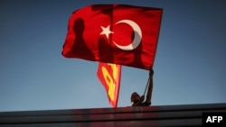 Turkey -- A man waves his national flag on Taksim square in Istanbul, 09Jun2013