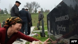 A woman cries at the grave of a relative killed during the April 2010 uprising at the Ata-Beyit cemetery, some 20 km outside the capital Bishkek, on April 7.