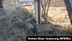 У электрического столба в беспорядке валяются камни, когда-то бывшие частью стены храма