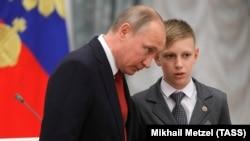 Владимир Путин и школьник Владислав Мартынов во время церемонии вручения российских паспортов молодым гражданам России. 12 июня 2017 года