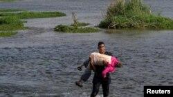 Menedékkérő venezuelai migráns, karjában egy idős nővel a Texast Mexikótól elválasztó Rio Grande folyón, 2021. május 26-án