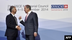 Switzerland -- Swiss President and OSCE Chairperson-in-office Didier Burkhalter (L) welcomes Russian Foreign Minister Sergei Lavrov at the opening of an OSCE ministerial meeting in Basel, December 4, 2014