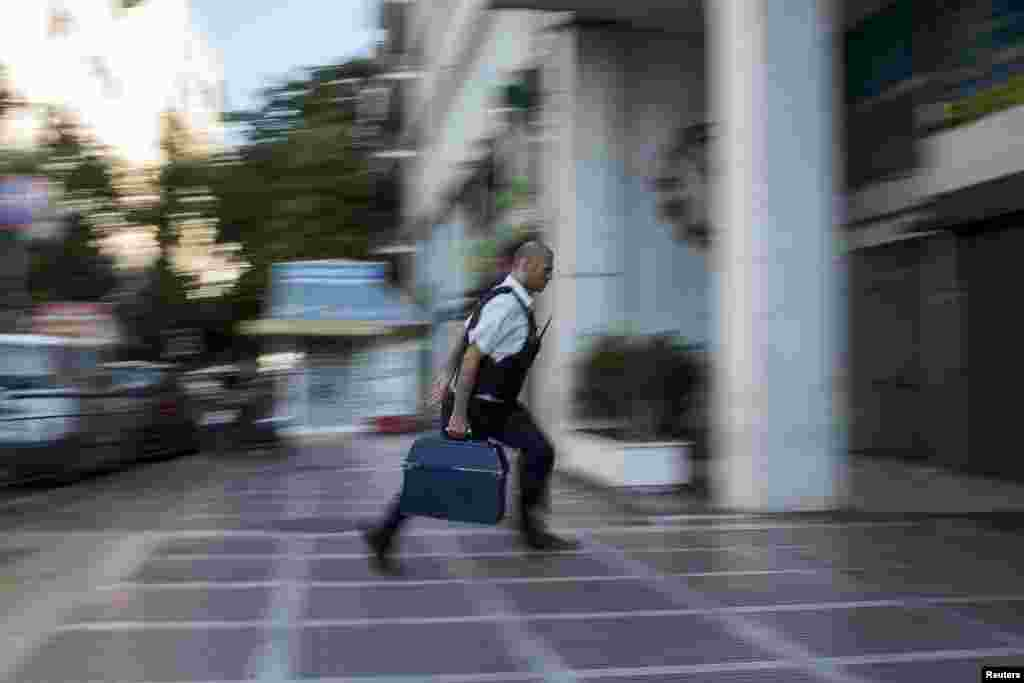 A security worker brings money to a National Bank branch in Athens, Greece, on June 29. Greece's European partners shut the door on extending a credit lifeline to Athens, leaving the country facing a default that could push it out of the euro and cause ripple effects across the European economy and beyond. (Reuters/Marko Djurica)
