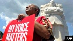 """رجل يحمل يافطة كتب عليها """"صوتي يؤثّر"""" أمام نصب لوثر كنغ"""