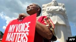 """Человек с плакатом, на котором написано """"Мой голос имеет значение"""", стоит у памятника Мартину Лютеру Кингу - младшему. Вашингтон, 24 августа 2013 года."""