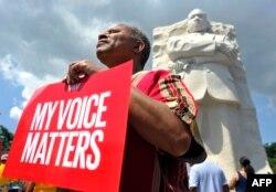 """Muškarac drži transparent """"Moj glas je važan"""" ispred spomenika dr. Kingu u Vašingtonu"""