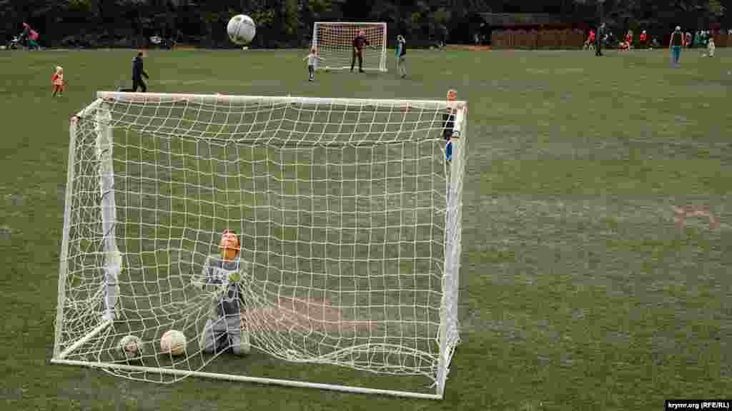 Футбольный мяч с подачи начинающего юного футболиста движется по непредсказуемой траектории