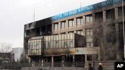 Прохожие рядом со сгоревшим зданием предприятия «Озенмунайгаз», дочерней компании «КазМунайГаза». Жанаозен, 17 декабря 2011 года.