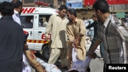Volunteers carry a victim to an ambulance from the site of a suicide attack during a Shi'ite procession in Quetta.