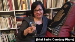 "Shadi Sadr sits on the ""Islamic"" couch with a wine glass."