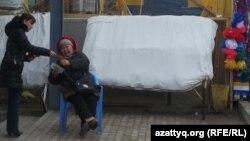 Женщина на рынке разменивает деньги покупателю. Актау, декабрь 2014 года.