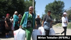 Женщины несут товары на казахско-кыргызской границе.