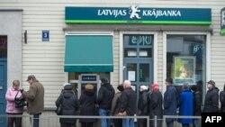 Люди у здания одного из коммерческих банков Латвии. Рига, 23 ноября 2011 года. Иллюстративное фото.