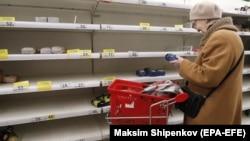 Женщина стоит у пустых полок в супермаркете. Москва, Россия.