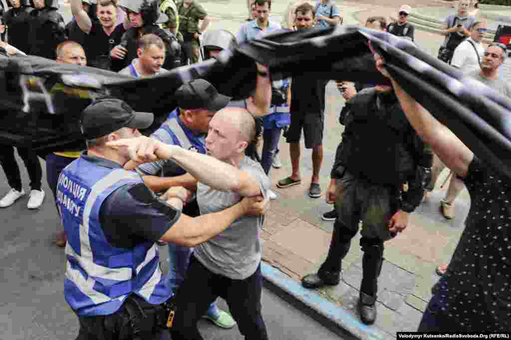 An anti-LGBT protester scuffles with security personnel at the Kyiv march.