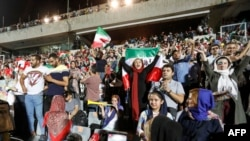 IRAN -- Iranian soccer supporters wave their national flags as they cheer for their national team during a screening of the Russia 2018 World Cup Group B football match between Iran and Spain in Azadi stadium in the capital Tehran, June 20, 2018