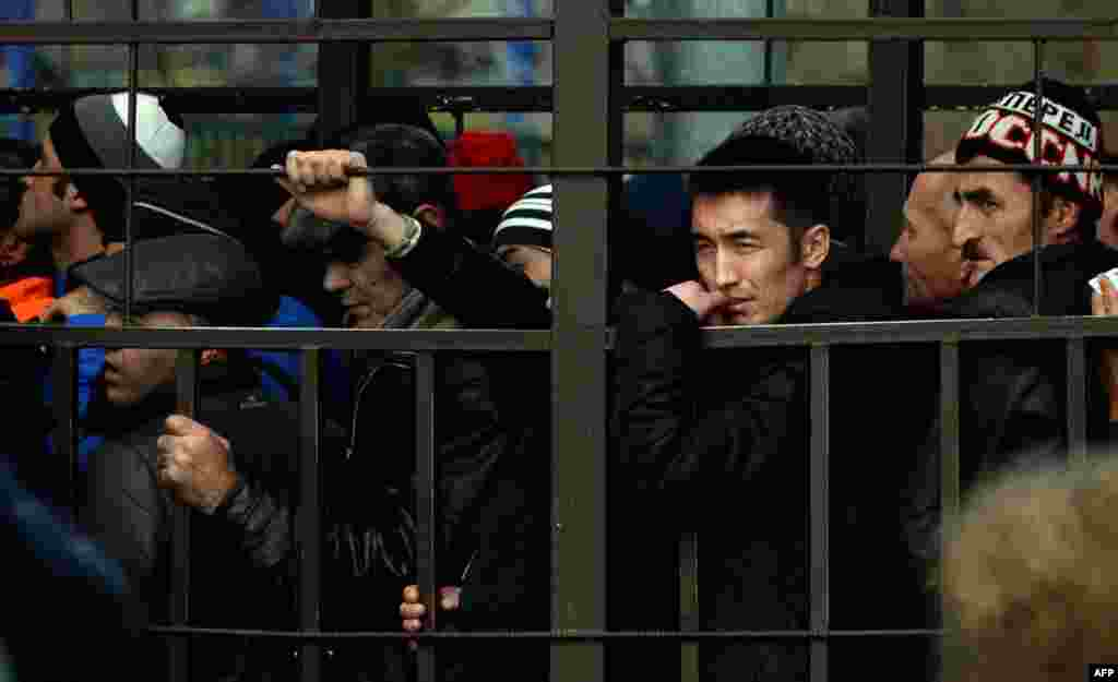 Migrant workers in Russia line up in a fenced holding area outside the Federal Migration Service (FMS) office in Moscow as they wait for their turn to get a work permit. (AFP/Vasily Maximov)