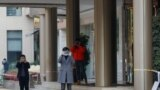 Kinseki službenici fotografišu fotografa ispred hotela u Vuhanu gdje su smješteni članovi tima Svjetske zdravstvene organizacije, 15. januar, 2021.