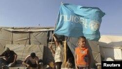 Сирийский ребенок с перевернутым флагом ЮНИСЕФ в лагере для беженцев.