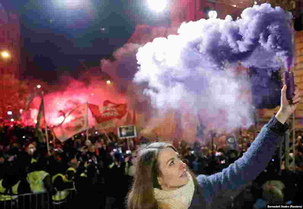 "Anna Donath, vice president of the opposition party Momentum Movement, holds a flare during a protest against a proposed new labor law, billed as the ""slave law,"" in Budapest. (Reuters/Bernadett Szabo)"