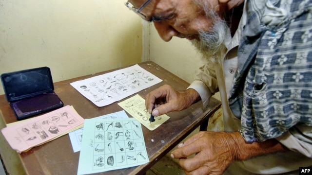 A Pakistani man marks his ballot in Karachi during elections in August 2005.