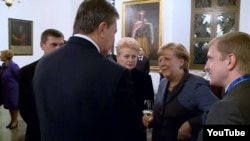 German Chancellor Angela Merkel, glass in hand, had an awkward exchange with Ukrainian President Viktor Yanukovych (center, back to camera) on the first day of the Third Eastern Partnership Summit in Vilnius on November 28.