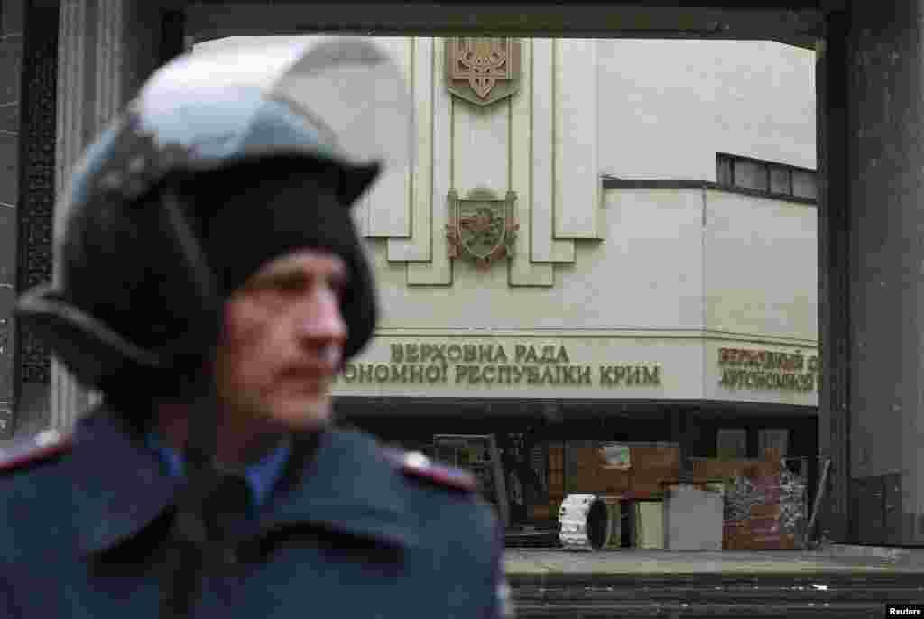 Сотрудник МВД стоит возле здания крымского парламента в Симферополе, который захватили неизвестные вооруженные люди.