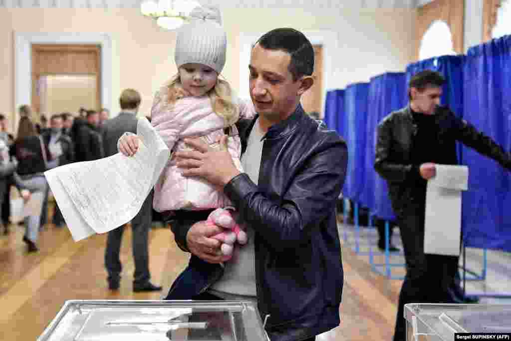 A little girl casts a man's ballot in Kyiv. (AFP/Sergei Supinsky)