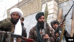 Former Taliban fighters attend a ceremony as they surrender their weapons.