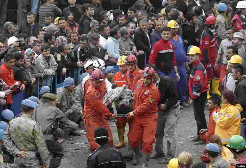 Спасатели выносят спасенного шахтера.